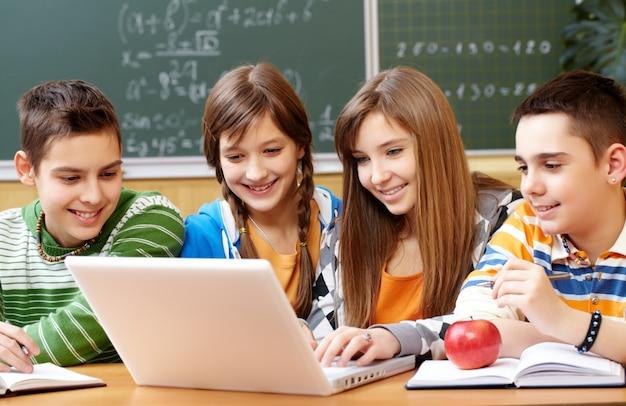 Estudantes que trabalham no laptop na escola