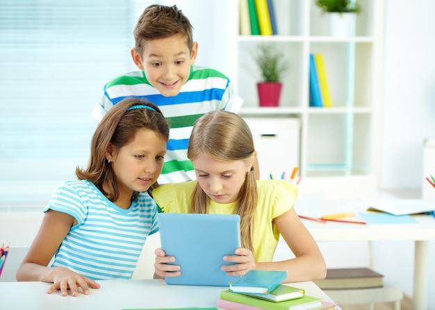 Estudantes que usam uma tabuleta digital na sala de aula