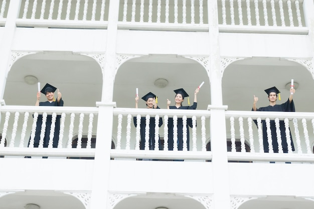 Estudantes se sentindo felizes com os vestidos de formatura ficam no prédio do corredor.