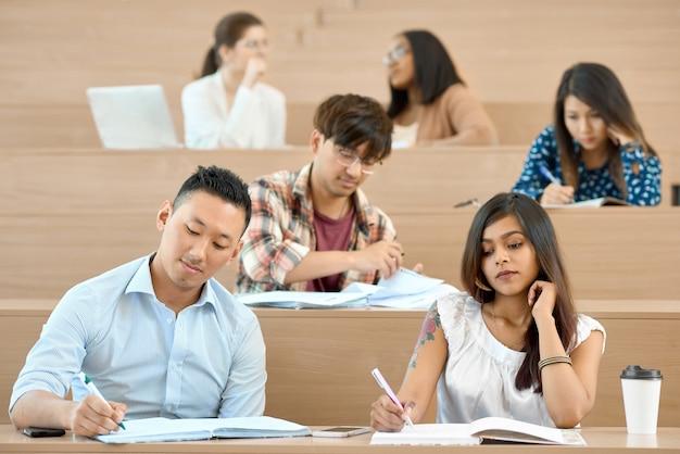 Estudantes sentados em mesas de madeira em sala de aula e estudar.