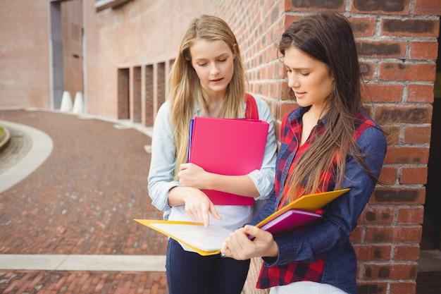 Estudantes sérios lendo livro na universidade