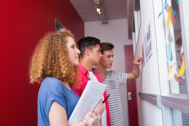 Estudantes sérios que estudam com gráficos na parede