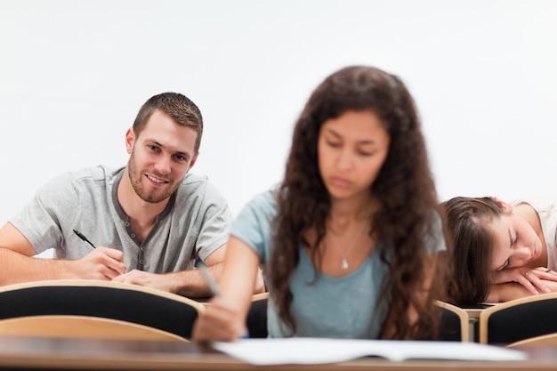 Estudantes sorridentes enquanto escrevem enquanto seu colega está dormindo