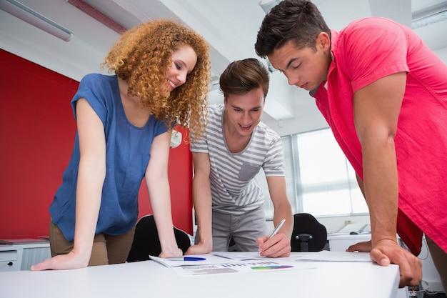 Estudantes sorridentes trabalhando e tomando notas juntos