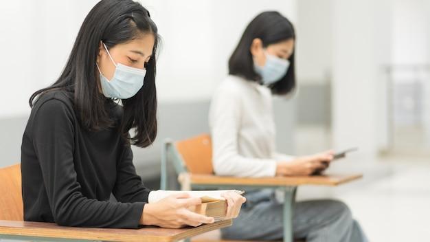 Estudantes universitárias adolescentes do sexo feminino usam máscara facial e mantêm distância enquanto estudam em sala de aula e no campus da faculdade para prevenir a pandemia de covid-19. foto de estoque de educação