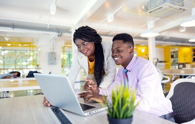 Estudantes universitários africanos usando laptop juntos.