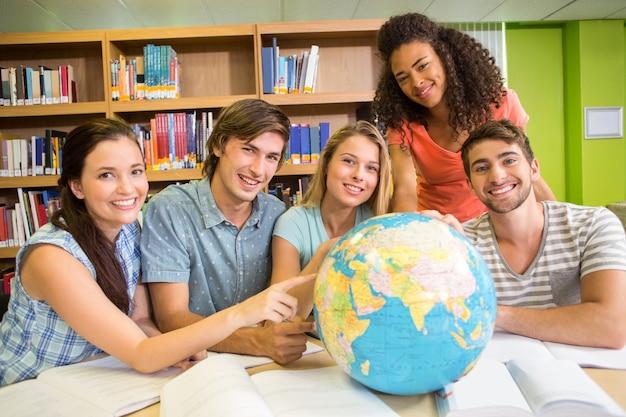 Estudantes universitários apontando para o globo na biblioteca