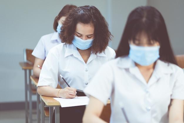 Estudantes universitários asiáticos adolescentes com máscara estudando na sala de aula