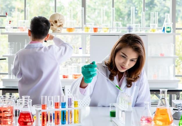 Estudantes universitários asiáticos concentrados conduzindo experimentos com líquidos coloridos durante pesquisas científicas em laboratório.