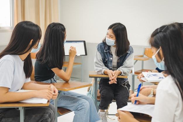 Estudantes universitários asiáticos do grupo usam máscara protetora e discutem o projeto em sala de aula