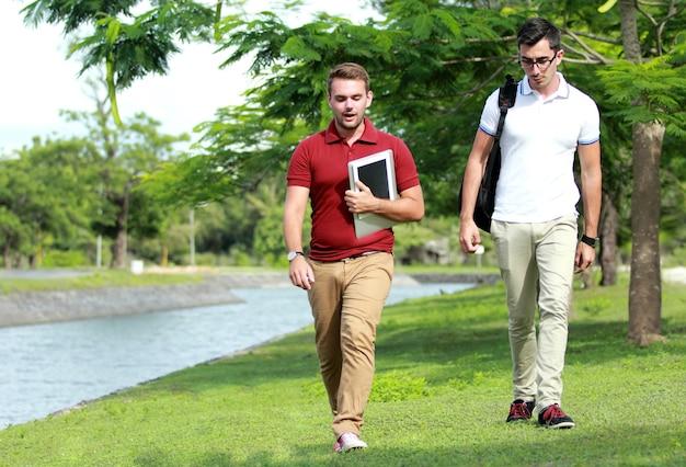 Estudantes universitários caminhando juntos na beira do rio