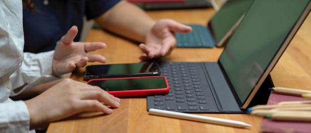 Estudantes universitários discutindo em seu projeto com informações sobre o smartphone enquanto trabalhava com tablet