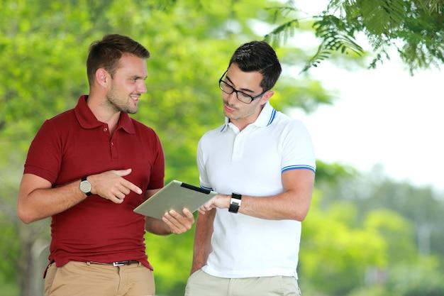 Estudantes universitários discutindo uma tarefa usando um tablet no parque da faculdade
