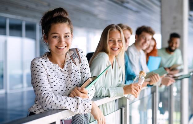 Estudantes universitários em pé e olhando para a câmera dentro de casa, de volta ao conceito de escola.