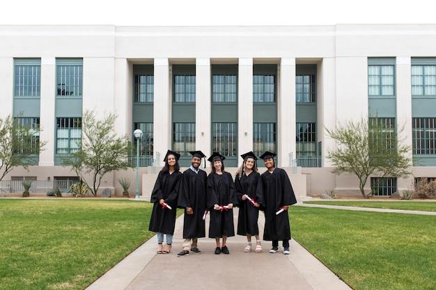 Estudantes universitários em vestidos de formatura