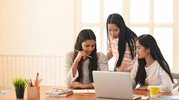Estudantes universitários estão fazendo e-learning enquanto estão sentados juntos na sala de estar.