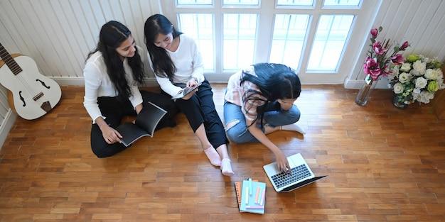 Estudantes universitários estão relaxando com um laptop e tablet na sala de estar.