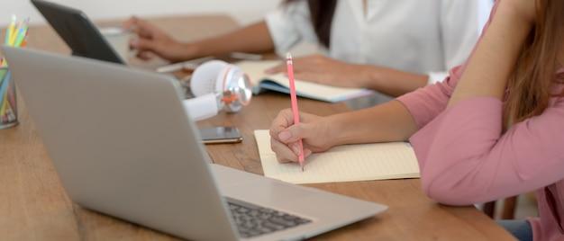 Estudantes universitários fazendo seu projeto em conjunto com dispositivos digitais e artigos de papelaria na mesa de madeira