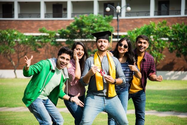 Estudantes universitários indianos asiáticos recebem certificado de graduação enquanto amigos comemoram no campus da faculdade ao ar livre