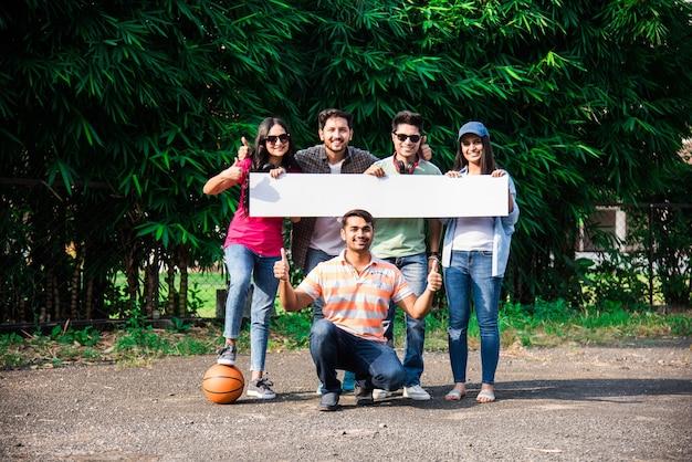 Estudantes universitários indianos asiáticos segurando ou mostrando um quadro branco ou cartaz vazio no campus da universidade, foto ao ar livre