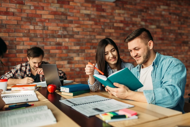 Estudantes universitários lendo livros juntos