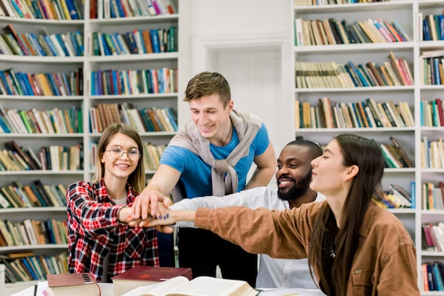 Estudantes universitários multirraciais, colocando as mãos em cima uns dos outros, simbolizando a unidade e o trabalho em equipe, sentados juntos na biblioteca