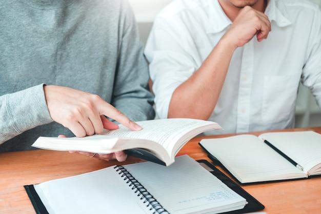 Estudantes universitários ou universitários estudando e lendo juntos na biblioteca.