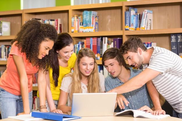 Estudantes universitários, usando computador portátil, em, biblioteca