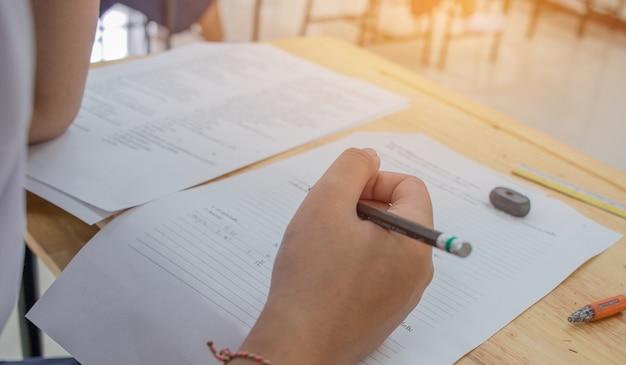 Estudantes usando lápis escrevendo informações em papel de resposta branco na escola secundária