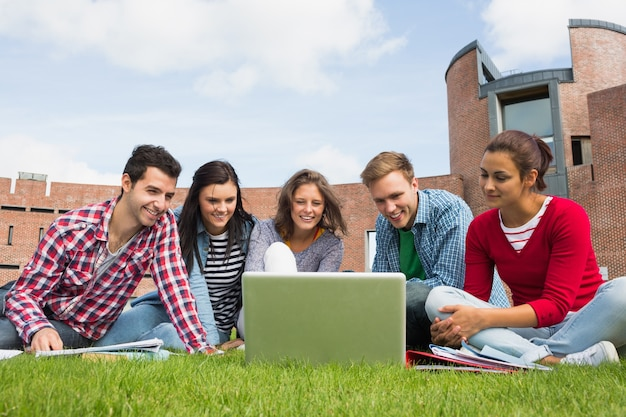 Estudantes usando laptop no gramado contra o edifício da faculdade