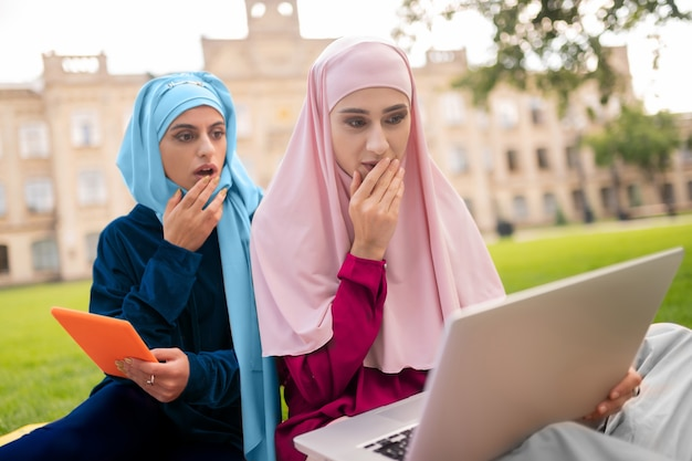 Estudar antes das aulas. alunos muçulmanos internacionais estudando antes das aulas juntos, sentados na grama