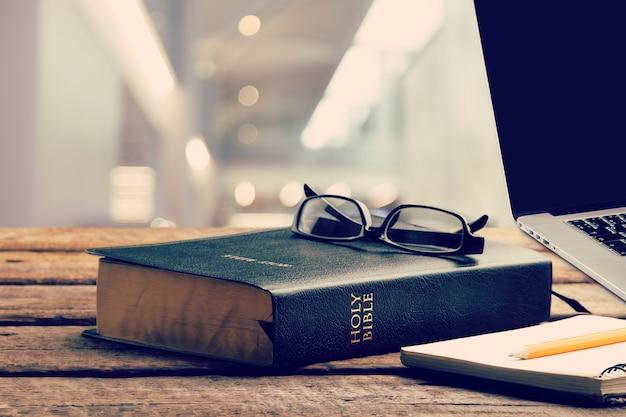Estude a bíblia com o laptop na mesa de madeira