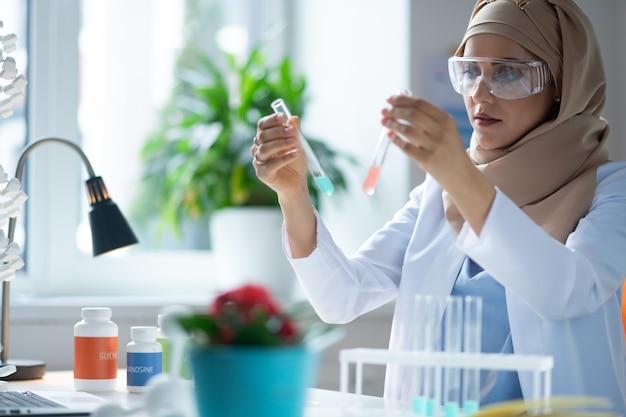 Estude agentes químicos. química feminina usando hijab, sentada perto da janela, estudando agentes químicos