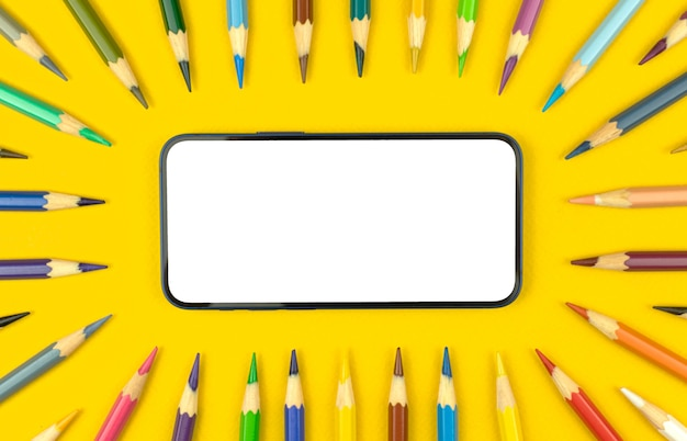 Estude o fundo da maquete com a tela branca em branco do telefone celular moderno e lápis de cor na área de trabalho da mesa, fundo amarelo, espaço de cópia e foto de vista superior