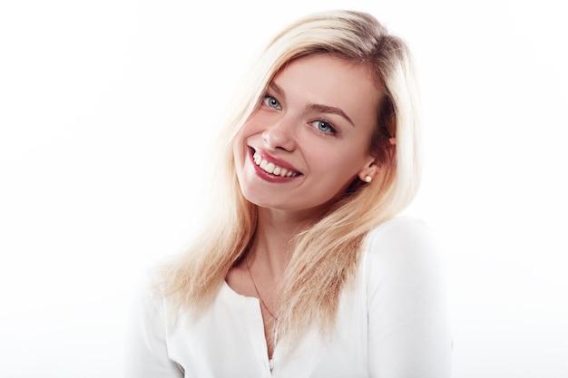 Estúdio ascendente próximo de sorriso da cara da mulher bonita no branco.