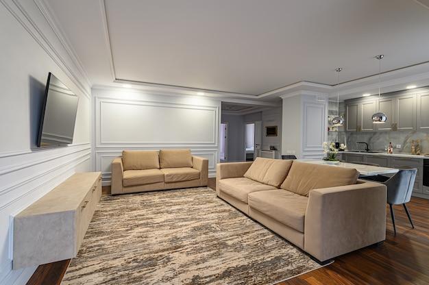 Estúdio contemporâneo em branco, cinza e bege com interior clássico e contemporâneo com mesa de jantar, sofá e tv