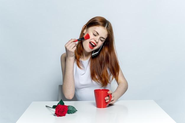 Estúdio criativo de uma linda mulher sentada à mesa caneca vermelha flor rosa