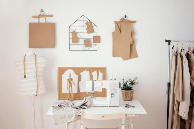 Estúdio de alfaiataria com máquina de costura e peças de roupa