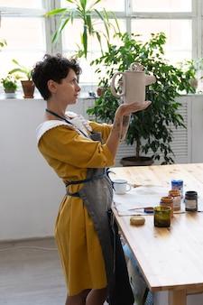 Estúdio de arte dentro de uma jovem artista feminina em avental ceramista trabalhando na oficina preparando jarra de argila de oleiro