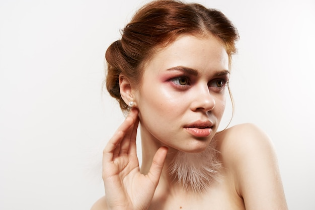Estúdio de brincos fofos com maquiagem brilhante e ombros nus de mulher alegre