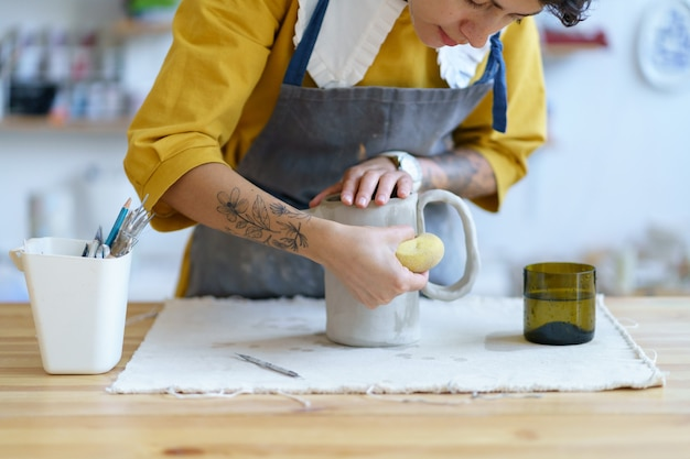 Estúdio de cerâmica dentro de uma garota artista de avental criando uma jarra de argila úmida segurando ferramentas profissionais