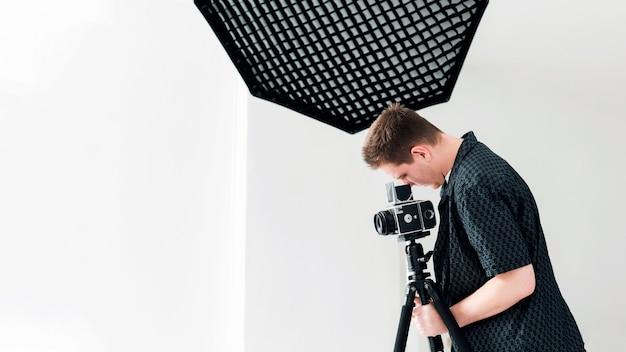 Estúdio de fotografia e homem trabalhando com suas câmeras