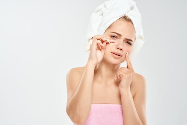 Estúdio de problemas de pele facial de uma linda mulher com uma toalha na cabeça