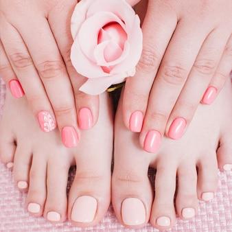 Estúdio de unhas. cuidado com os pés. manicure e pedicure. pés de mãos femininas. verniz de cor pêssego.