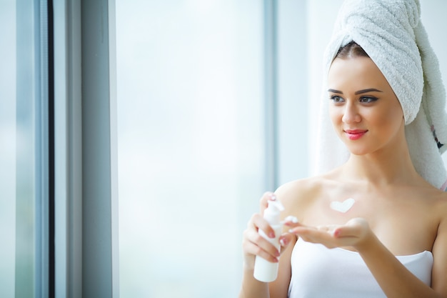 Estúdio disparado da mulher bonita de aplicar o creme hidratante no rosto no banheiro moderno