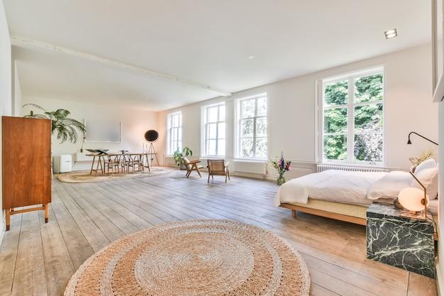 Estúdio espaçoso com cama e guarda-roupa sob a janela do teto e porta aberta que leva ao jardim verde.