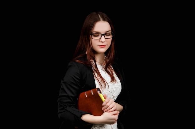 Estúdio fechar o retrato de uma garota de aparência eslava, vestindo uma jaqueta preta e óculos em um fundo preto com um caderno marrom nas mãos dela.