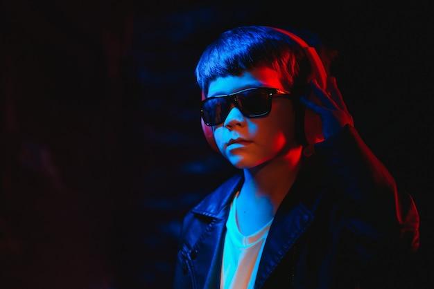 Estúdio filmado em estúdio escuro com luz de néon. retrato de um menino estiloso com fones de ouvido