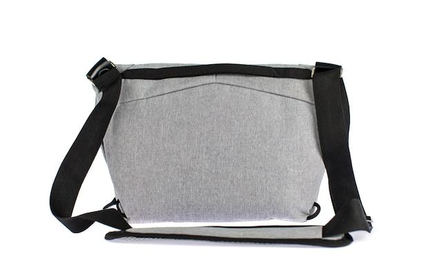 Estúdio isolado closeup tiro de novo pequeno casual moderno moderno na moda tecido cinza mensageiro rider homens estilingue bolsa de bagagem com alça e etiqueta cinza vazio na frente do fundo branco.