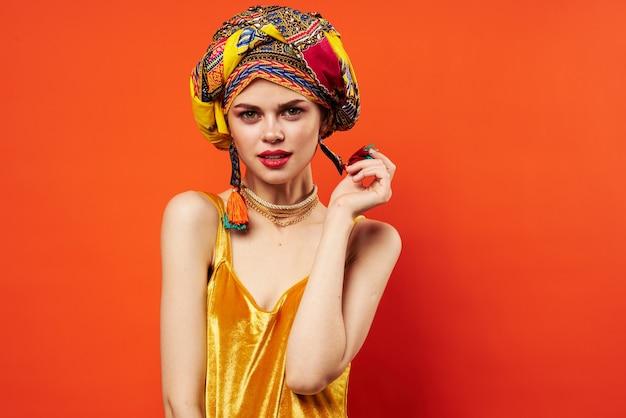 Estúdio luxuoso do fundo vermelho do turbante multicolorido da decoração da mulher bonita.
